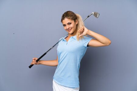 Teenager golfer girl over grey wall proud and self-satisfied Archivio Fotografico