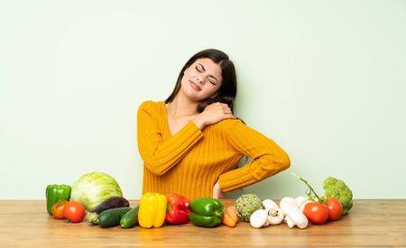 Teenager girl with many vegetables suffering from pain in shoulder for having made an effort