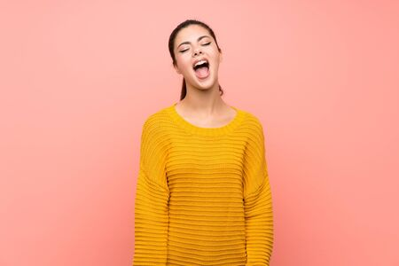 Teenager girl over isolated pink wall shouting to the front with mouth wide open Imagens