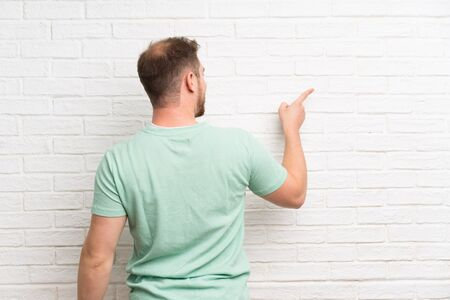 Blonde man over brick wall pointing back with the index finger