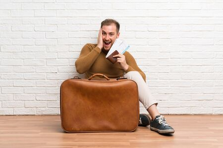 Traveler man with suitcase and boarding pass with surprise and shocked facial expression