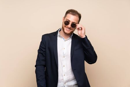 Blonde man over isolated background with glasses and happy