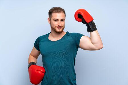 Sportivo biondo sul muro blu con guantoni da boxe