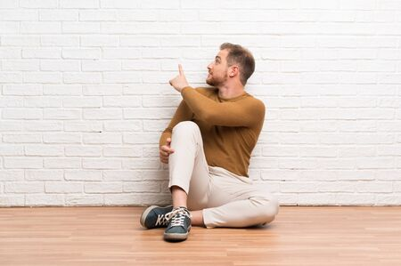 Blonde man sitting on the floor pointing back with the index finger