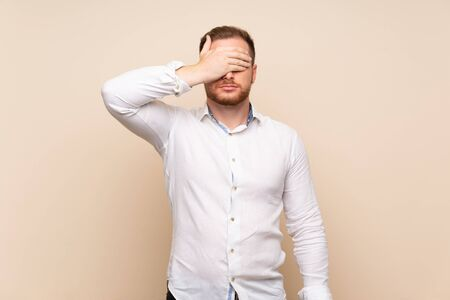 Blonde man over isolated background covering eyes by hands. Do not want to see something