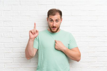 Blonde man over brick wall with surprise facial expression