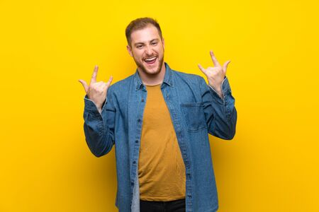 Blonde man over isolated yellow wall making rock gesture