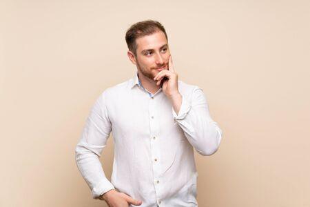 Blonde man over geïsoleerde achtergrond denkt aan een idee terwijl hij omhoog kijkt