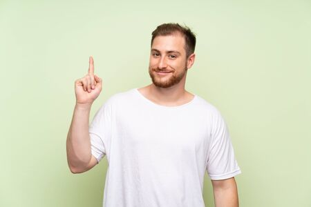 Handsome man over green background pointing with the index finger a great idea