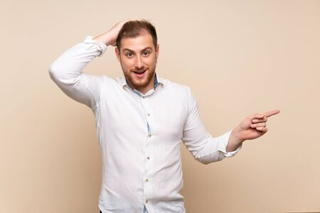 Blonde man over isolated background surprised and pointing finger to the side Stock Photo