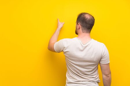 Handsome man over yellow background pointing back with the index finger