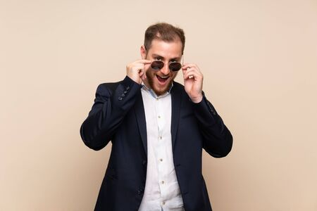 Blonde man over isolated background with glasses and surprised