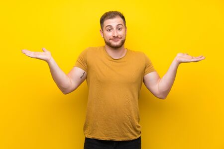 Blonde man over isolated yellow wall having doubts while raising hands Foto de archivo