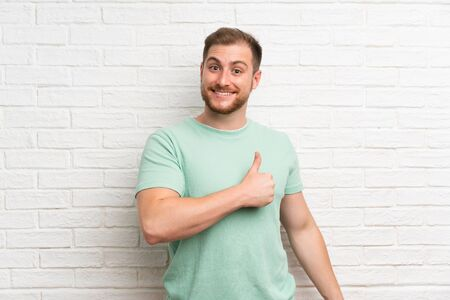 Blonde man over brick wall giving a thumbs up gesture
