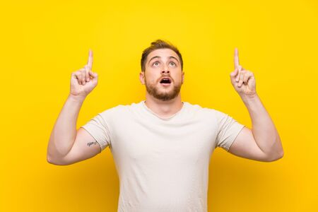 Handsome man over yellow background pointing with the index finger a great idea