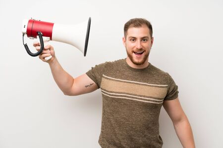 Handsome man over isolated white wall holding a megaphone Banco de Imagens