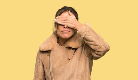 Blonde woman with a coat covering eyes by hands. Do not want to see something over isolated yellow background
