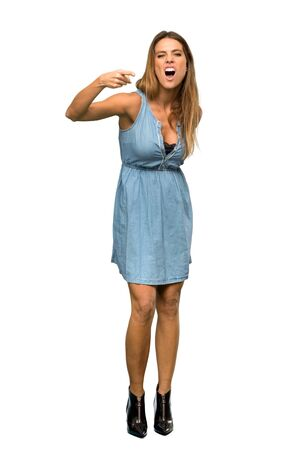 A full-length shot of a Blonde woman with jean dress frustrated and pointing to the front over isolated white background