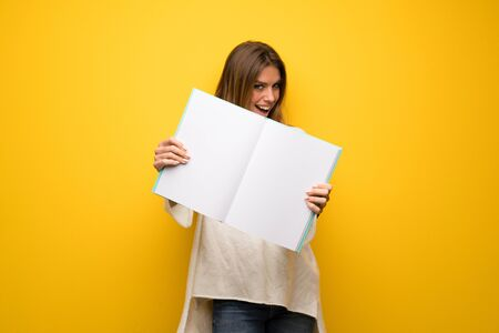Blonde woman over yellow wall holding an empty white placard Stock Photo