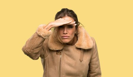 Blonde woman with a coat looking far away with hand to look something over isolated yellow background