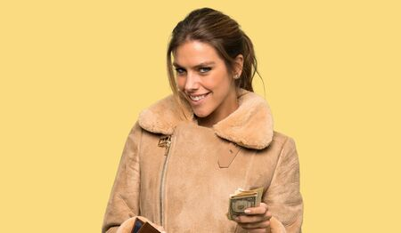 Blonde woman with a coat holding a wallet over isolated yellow background Stock Photo