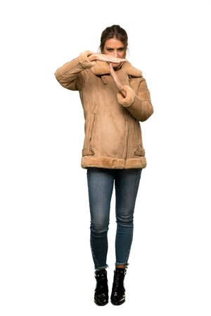 A full-length shot of a Blonde woman with a coat making time out gesture over isolated white background