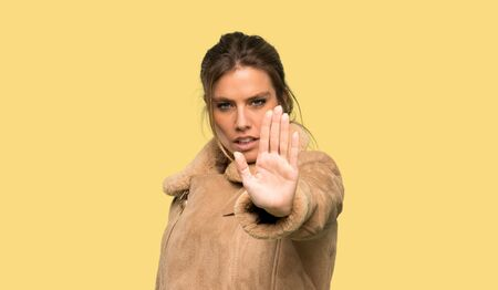 Blonde woman with a coat making stop gesture denying a situation that thinks wrong over isolated yellow background