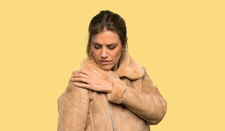 Blonde woman with a coat suffering from pain in shoulder for having made an effort over isolated yellow background Standard-Bild
