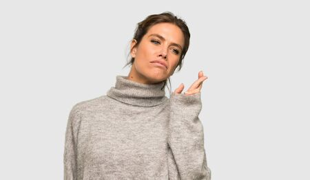 Blonde woman with turtleneck with fingers crossing and wishing the best over isolated grey background Stock Photo