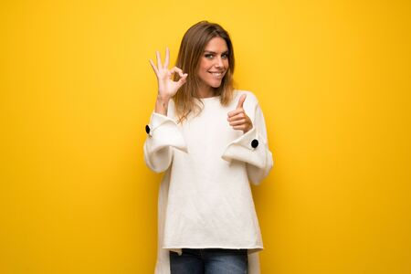 Blonde woman over yellow wall showing ok sign with and giving a thumb up gesture Stock Photo