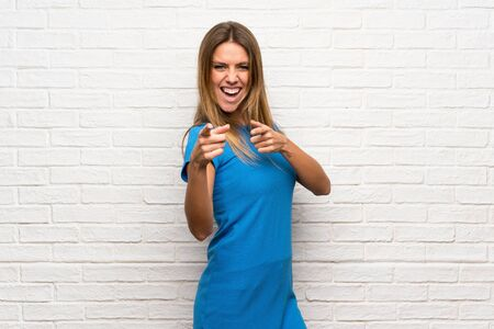 Woman with blue dress over brick wall pointing to the front and smiling Stock Photo