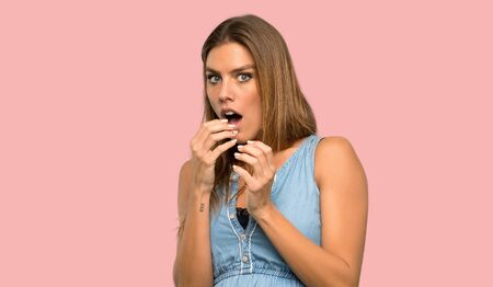 Blonde woman with jean dress nervous and scared putting hands to mouth over isolated pink background Stock Photo