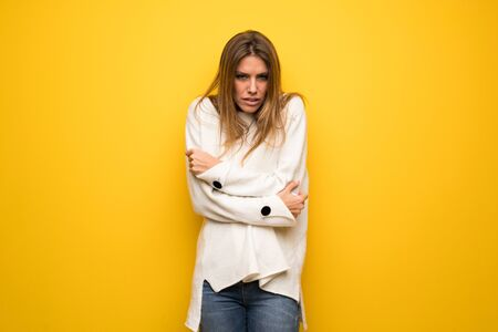 Blonde woman over yellow wall freezing