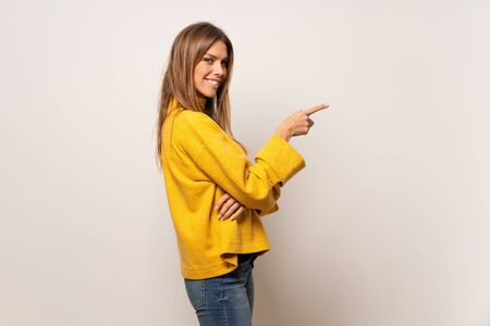 Woman with yellow sweater over isolated wall pointing finger to the side