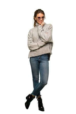 A full-length shot of a Blonde woman with turtleneck with glasses and smiling over isolated white background 写真素材
