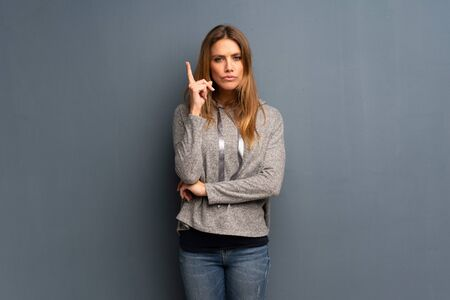 Blonde woman over grey background thinking an idea pointing the finger up