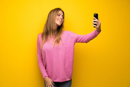 Woman with pink sweater over yellow wall making a selfie Stock Photo