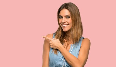 Blonde woman with jean dress pointing to the side to present a product over isolated pink background