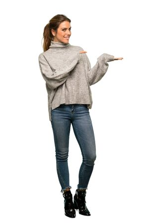 A full-length shot of a Blonde woman with turtleneck holding copyspace imaginary on the palm to insert an ad over isolated white background Foto de archivo - 129993729