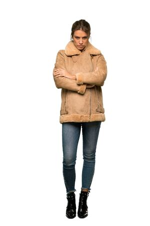 A full-length shot of a Blonde woman with a coat frustrated by a bad situation over isolated white background Foto de archivo - 129993734