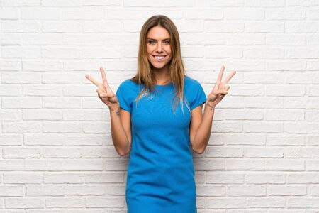 Woman with blue dress over brick wall smiling and showing victory sign with both hands Foto de archivo - 129993849