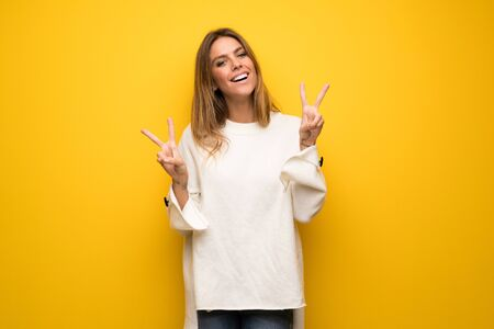 Blonde woman over yellow wall smiling and showing victory sign with both hands Foto de archivo - 129995451