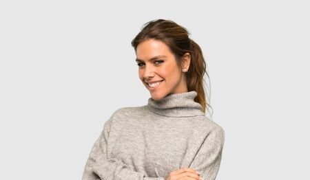 Blonde woman with turtleneck with arms crossed and looking forward over isolated grey background Foto de archivo - 129995512