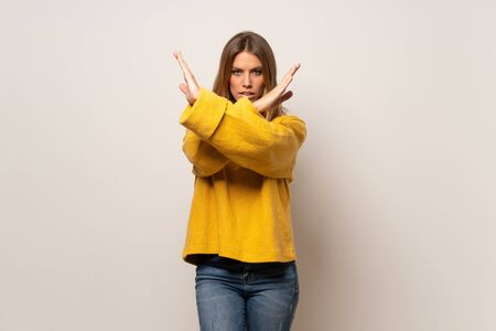Woman with yellow sweater over isolated wall making NO gesture