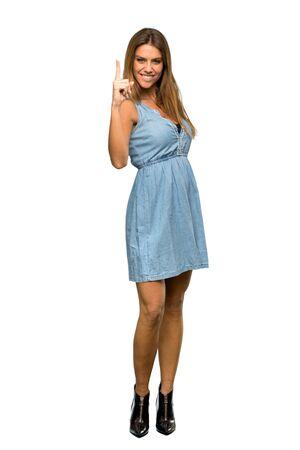 Une photo pleine longueur d'une femme blonde avec une robe en jean montrant et levant un doigt en signe du meilleur sur fond blanc isolé