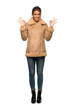 A full-length shot of a Blonde woman with a coat showing ok sign with fingers over isolated white background Stockfoto