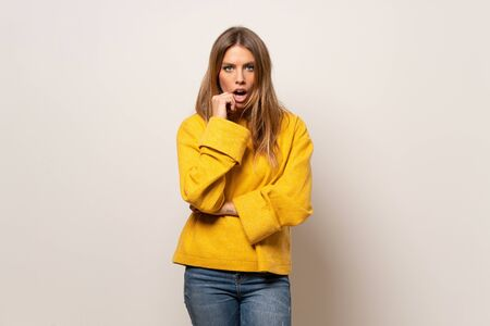 Woman with yellow sweater over isolated wall surprised and shocked while looking right