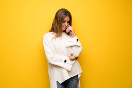 Blonde woman over yellow wall looking down with the hand on the chin