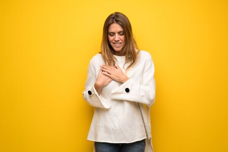 Blonde woman over yellow wall having a pain in the heart