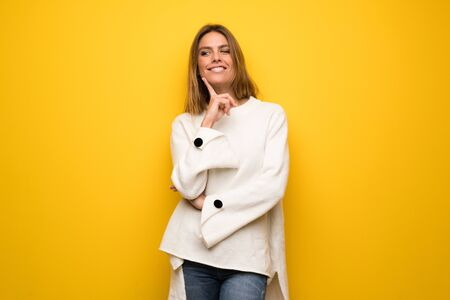 Blonde woman over yellow wall thinking an idea while looking up